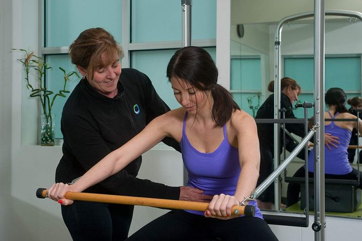 Judy Malcolm owner Perfect Fit Pilates instructing student Lucin on a Reformer.