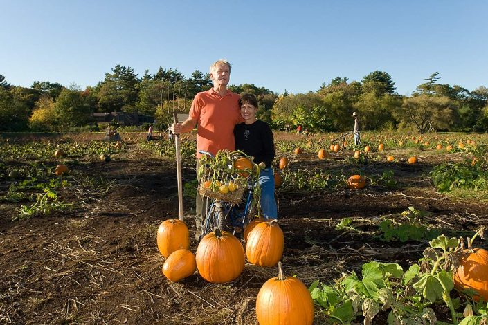 Middle aged couple posing for picture in pumkin patch at CobWebb