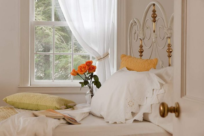 Romantic bedroom with a white iron headboard  and roses next to