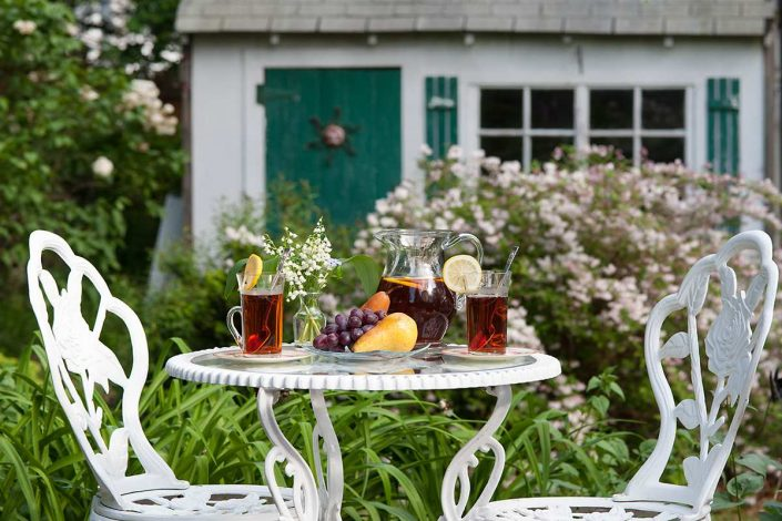 Fruit and ice tea outside on a white wrought iron table in a garden setting.